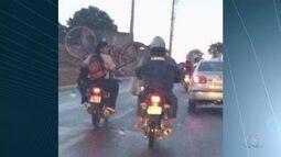 Motociclista é flagrado transportando bicicleta com pneus para cima; vídeo