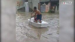 Homem usa caiaque em rua de Nova Iguaçu após chuva forte