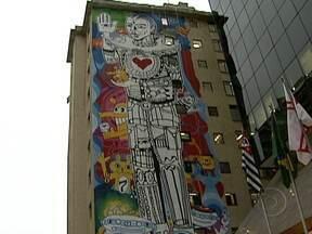 Painel grafitado em fachada de prédio chama atenção da capital paulista - O tamanho e as cores do desenho chama atenção das pessoas que passam pelas ruas da cidade. Na Avenida Paulista, um painel de 36 metros foi desenhado em um edifício. As obras são autorizadas pela prefeitura, que avalia o projeto do artista.