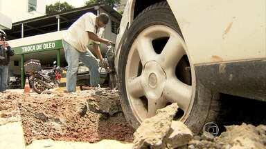 Concreto é retirado das rodas do carro cimentado em calçada de BH - Carro parado em calçada de obra estava preso no local