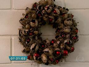 Arranjos preparados com flores podem incrementar a decoração de Natal - A guirlanda de parede montada com coroa de palha, cascas de sementes de palmeira, bolinhas e fios de bromélia é uma das sugestões para deixar a casa enfeitada no Natal.