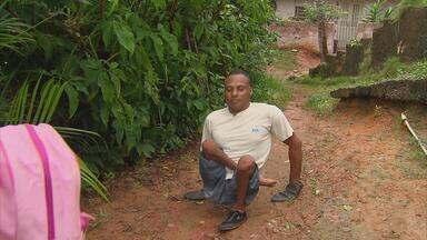 Morador de Camaragibe que tem deficiência luta para melhorar o lugar onde vive - No caminho, mato alto, muito barro, escadaria precisando de manutenção e água suja de esgoto.