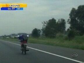Motociclista é flagrado pilotando deitado na BR-101 - Motociclista é flagrado pilotando deitado na BR-101