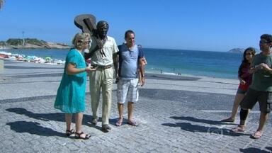 Turistas e cariocas disputam espaço para tirar foto com estátua do Tom Jobim - Um dia depois da inauguração, a estátua de Tom Jobim já se incorporou à paisagem de Ipanema. Turistas e cariocas disputam espaço para tirar foto com a estátua.