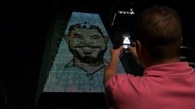 """Exposição tem caricaturas gigantes feitas em tempo real em prédio de São Paulo - Cem mil lâmpadas de led cobrem os 13 andares do prédio da FIESP. Os desenhos feitos em tempo real fazem parte da mostra """"Interativa Natureza Urbana""""."""
