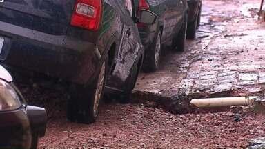 Rodas de carro ficam presas dentro de buraco após asfalto ceder - O carro estava estacionado no Centro de Ponta Grossa