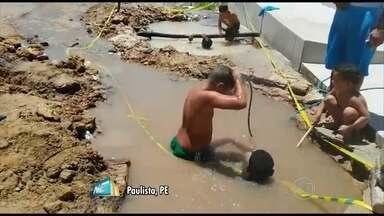 Imagens mostram crianças brincando em buracos com água em Paulista - Moradores dizem que buracos foram abertos após um vazamento de cano há 23 dias.