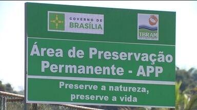 Obras na orla do Paranoá são retomadas - A placa voltou a demarcar a área de preservação ambiental. E as obras da ciclovia não param. São 33 hectares de área verde na beira do lago, na QL-12