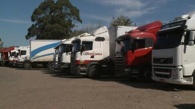 Crise econômica diminui movimento nas transportadoras do RS - Os caminhões estão parados no pátio.