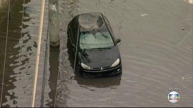 Pontos de alagamento permanecem na Avenida dos Democráticos - Após longa chuva, algumas ruas do Rio permanecem com pontos de alagamento. Na Avenida dos Democráticos, um carro está abandonado em meio à água.
