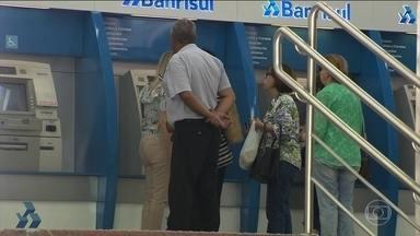 Funcionários públicos de Porto Alegre começam a receber o 13º atrasado - As agências bancárias abriram duras horas antes para fazer os pagamentos. A Justiça liberou a operação que estava sendo negada pelo banco.