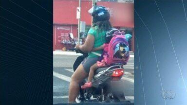 Motociclista transporta criança na garupa de moto, em Rio Verde - Uma espécie de fita amarrava as duas pela cintura.