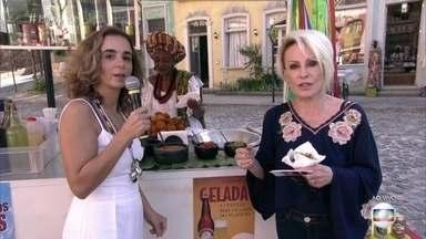 Ana Maria e Maria de Médicis comem acarajé na cidade cenográfica de 'Segundo Sol' - Apresentadora se diverte ao ver a barraca da cocada com alguns doces cenográficos feitos de vela