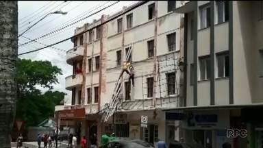 Trabalhadores ficam preso por uma corda enquanto faziam reforma - Segundo um morador, eles estavam apoiados em uma estrutura de ferro que caiu.