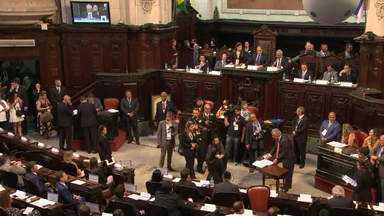 Alerj começa nova legislatura em meio à polêmica de deputados - Nesta sexta-feira (01), a maior parte dos 70 deputados eleitos tomou posse. Seis não foram à Alerj porque estão presos. Porém, a Assembleia pode decidir dar o cargo a eles assim mesmo.