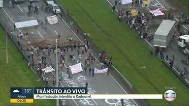 Moradores protestam no Rodoanel e rodovia fica fechada por mais de uma hora em São Paulo - Faixas e inscrições na pista do Rodoanel pedem asfalto e saída do subprefeito de Capela do Socorro. Subprefeito promete conversar com os manifestantes.