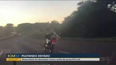 Motociclista é flagrado pilotando a moto deitado - Ele foi abordado e levou multa de quase R$ 3 mil.
