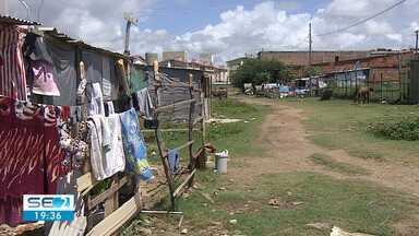 Famílias que moram em ocupação em Aracaju dizem que não têm para onde ir - Após uma ação de reintegração de posse, os ocupantes receberam notificação para deixar um terreno, que pertence à prefeitura.