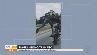 Homem empina moto no Anel Rodoviário de Belo Horizonte - Ele fica em pé, se exibe, empina a moto com uma das pernas no ar e chega a trocar de faixa ainda fazendo as manobras.