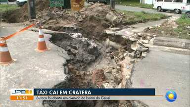 Cratera se abre em asfalto e carro fica pendurado, em João Pessoa - Táxi passava no local quando o asfalto cedeu.
