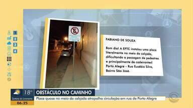 Placa quase no meio da calçada atrapalha circulação em rua de Porto Alegre - EPTC afirma que placa foi colocada nesta posição para que veículos não batam. Empresa diz que vai reajustar posicionamento da sinalização.
