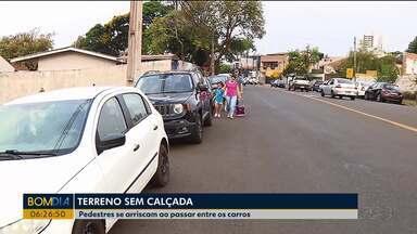 Falta de calçada perto de escola traz perigo aos pedestres - Eles se arriscam ao passar entre os carros.