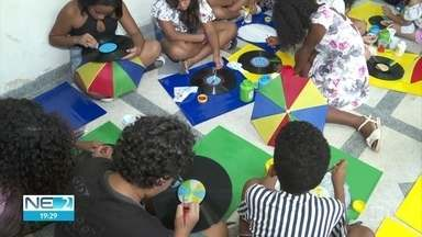 Crianças ajudam a fazer a fantasia do galo gigante - Elas estão pintando os discos de vinil que farão parte da roupa da alegoria