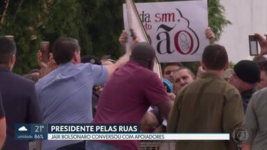 Sem máscara, presidente Jair Bolsonaro cumprimenta apoiadores em frente ao Planalto - Na chegada ao Palácio da Alvorada, Bolsonaro colocou a mão no rosto e pegou o celular de uma pessoa. Ninguém usava máscara.