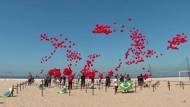 Ato em Copacabana homenageia os 100 mil mortos pela Covid-19 - Na areia, cruzes pretas e mil balões vermelhos simbolizavam as vidas que se foram. Um cartaz questionava o porquê de tantas vítimas no país.