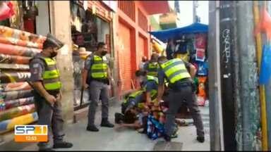 """Vídeo mostra PMs imobilizando ambulante que não queria entregar mercadorias em São Paulo - A POLÍCIA DE SÃO PAULO ESTÁ APURANDO O QUE ACONTECEU EM UMA ABORDAGEM DA """"PM"""" NA REGIÃO DA RUA 25 DE MARÇO, NO CENTRO DA CAPITAL./O VÍDEO MOSTRA UM AMBULANTE RESISTINDO À FISCALIZAÇÃO./VÁRIOS POLICIAIS APARECEM TENTANDO IMOBILIZAR UM HOMEM QUE ESTÁ CAÍDO NO CHÃO./ELE REAGE E RESISTE./DE ACORDO COM TESTEMUNHAS, A ABORDAGEM FOI ONTEM./SEGUNDO A """"PM"""", OUTRAS IMAGENS, QUE NÃO FORAM DIVULGADAS, MOSTRAM O HOMEM AGREDINDO FISCAIS DA PREFEITURA./O CASO AINDA VAI SER INVESTIGADO.//"""