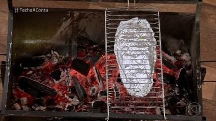 Cozinheiros preparam churrasco de peixe