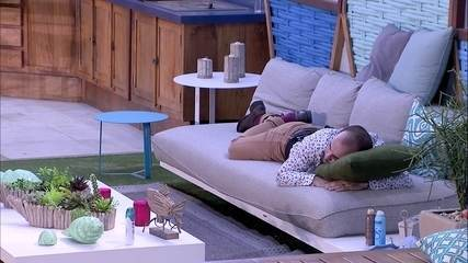 Mahmoud escuta música deitado no sofá da área externa