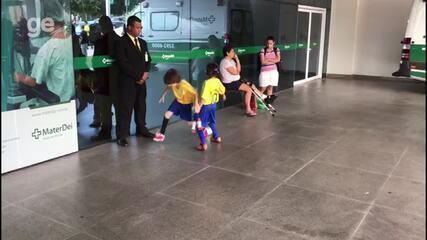 Com camisa da Seleção, crianças batem bola em frente a hospital que Neymar será operado