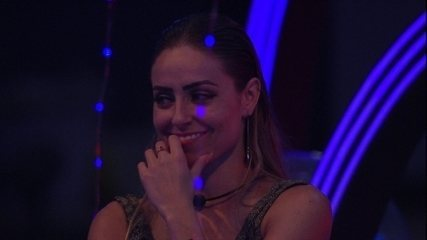 Paula vê sua retrospectiva no telão da Festa Internet e sorri