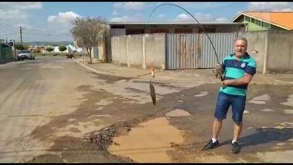 Morador 'pesca' em cratera na rua para protestar em Boituva