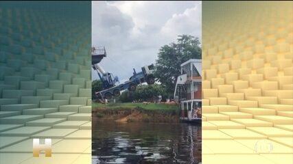 Caminhão vira e joga barco no rio, no interior de Rondônia