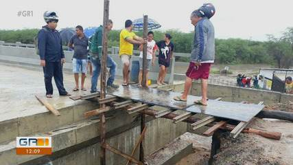 Após chuva, moradores de Bodocó improvisam passarela por cima de ponte em construção.