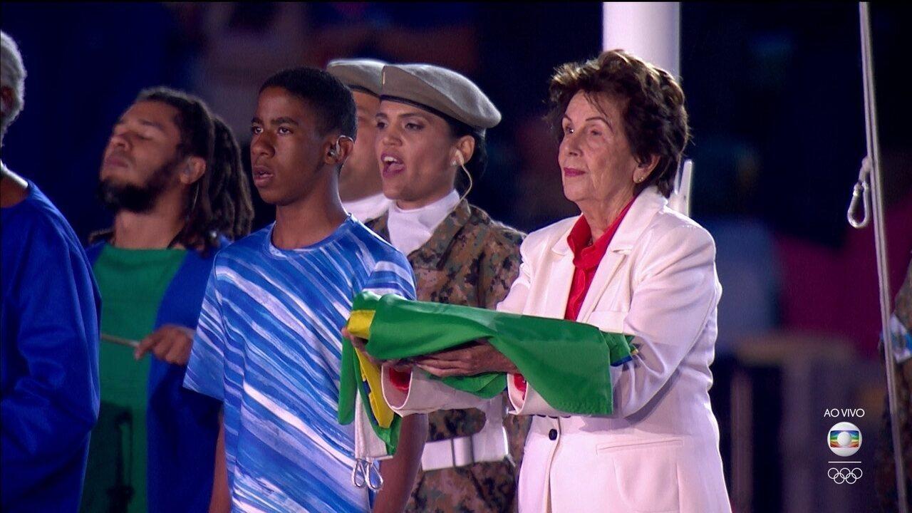 Coral canta hino nacional ao ritmo dos atabaques, e Maria Esther Bueno leva bandeira