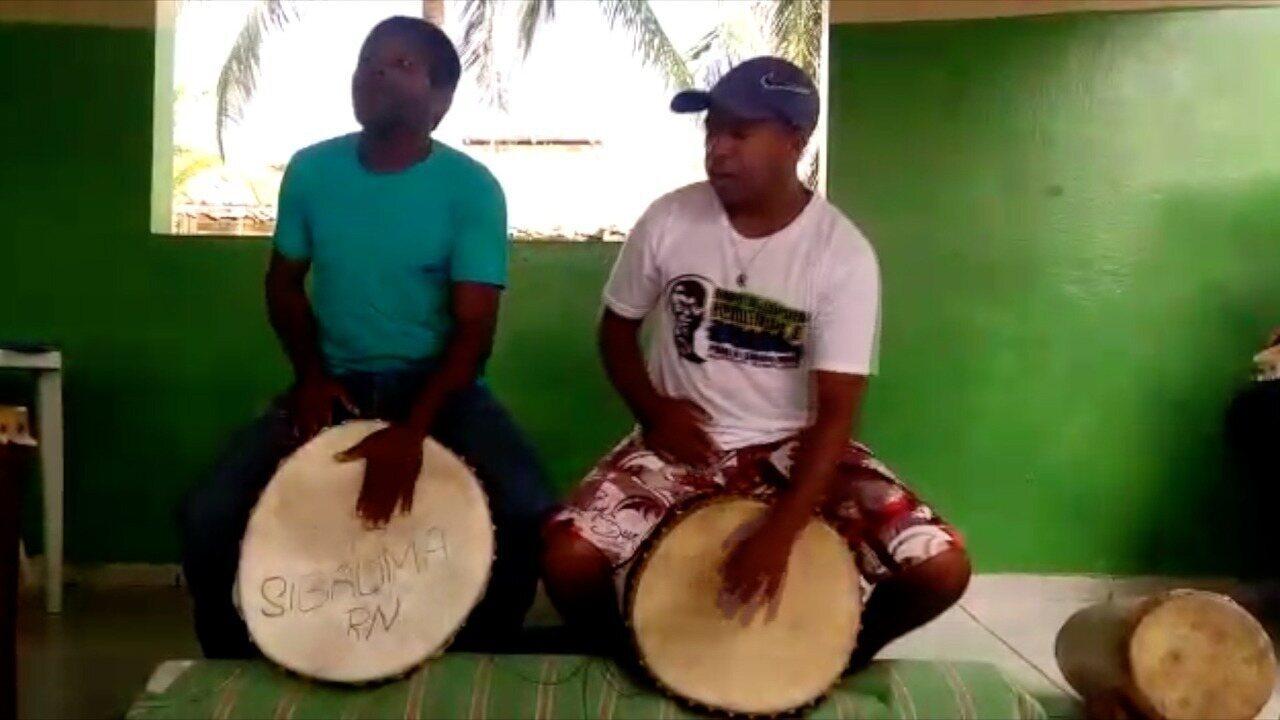 Sérgio Caetano e professor de capoeira da comunidade tocam canções ao som de tambores