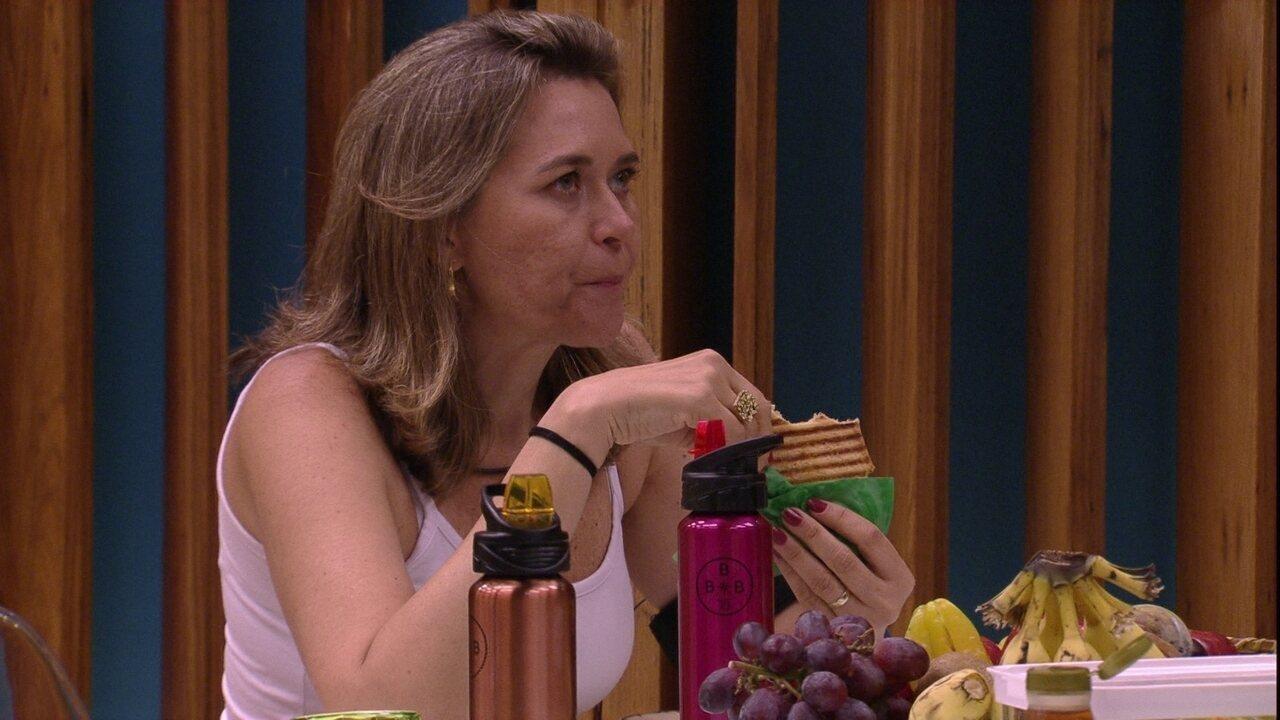 Eva come sanduíche enquanto conversa com Jorge