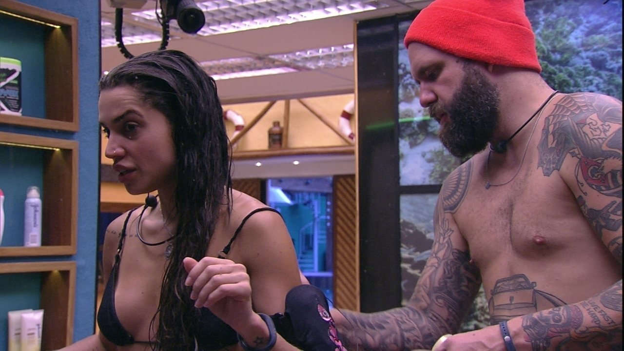 Caruso passa hidratante nas costas de Paula