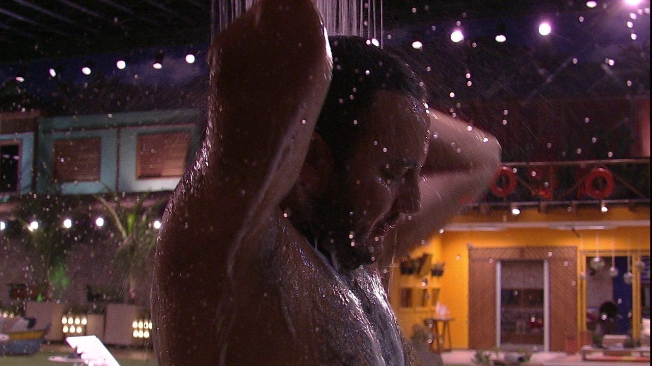 Diego toma banho no chuveiro do jardim