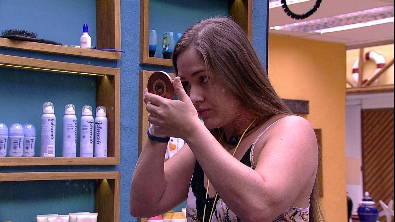 Patrícia passa maquiagem em frente ao espelho