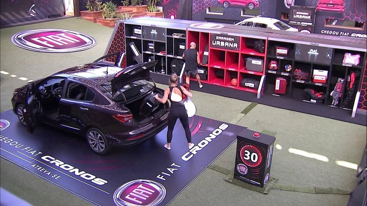 Jéssica e Kaysar esvaziam o bagageiro do Fiat Cronos Vermelho Marsala