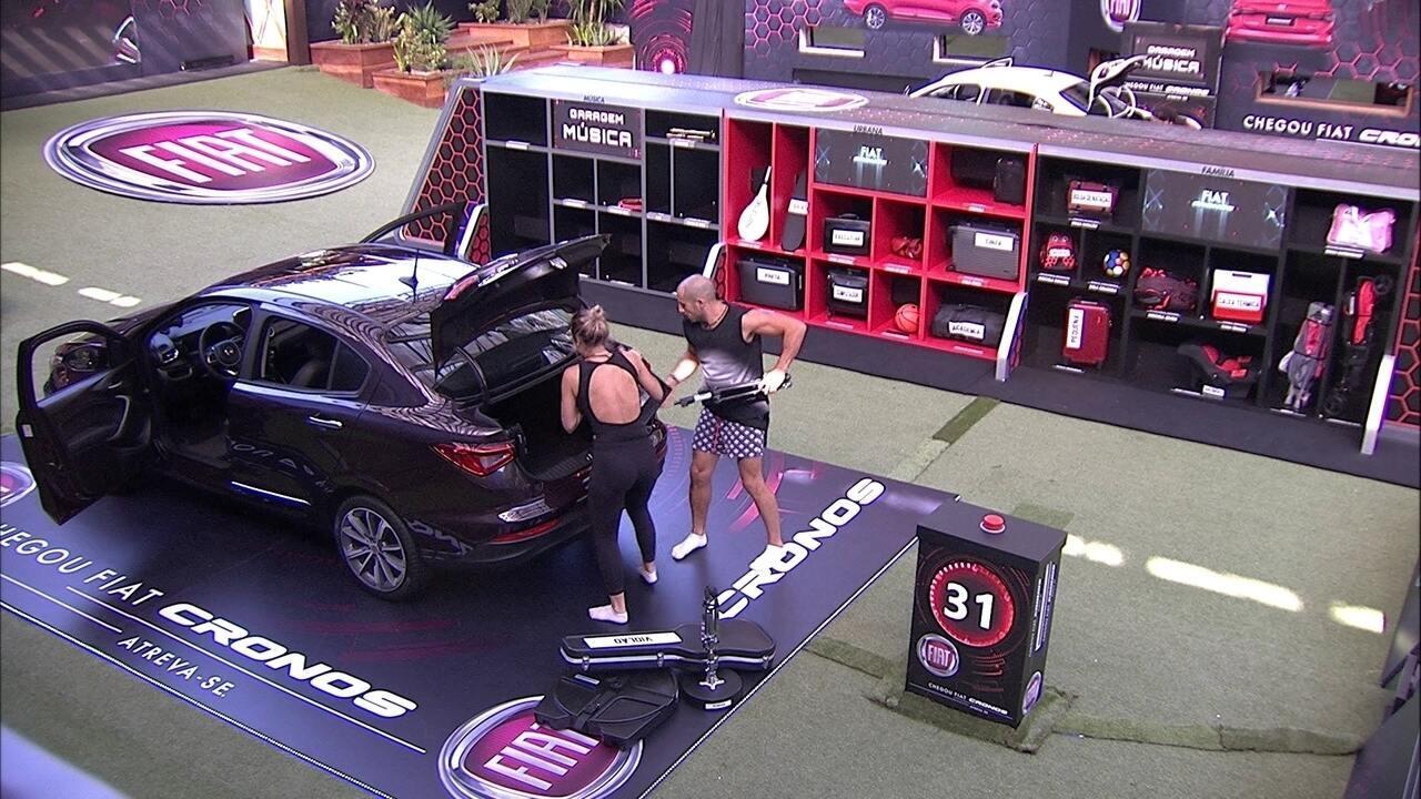Kaysar e Jéssica acomodam objetos no porta-malas do Fiat Cronos Vermelho Marsala