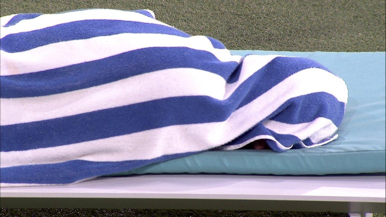 Ayrton deita em espreguiçadeira e se cobre com toalha