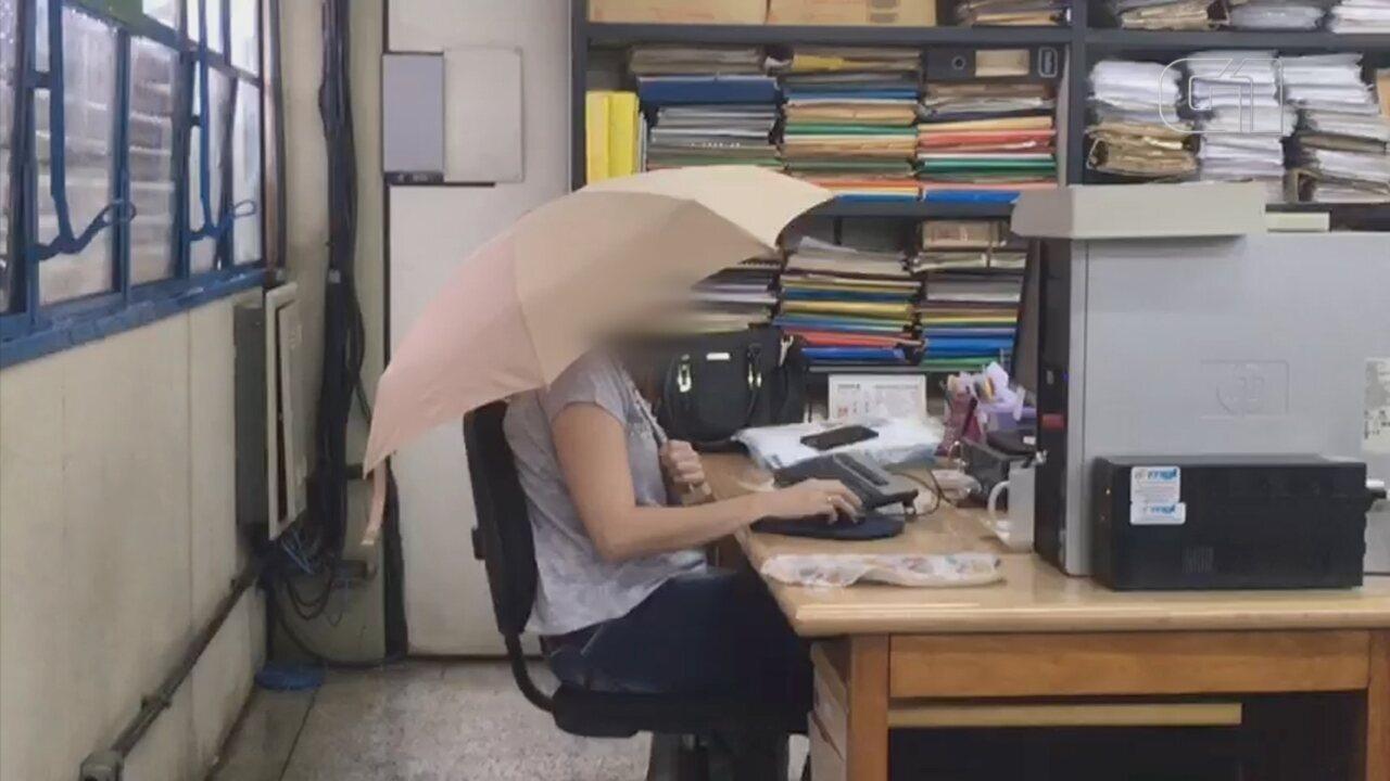 Funcionária de secretaria municipal de Bauru usa guarda-chuva para se proteger de goteira