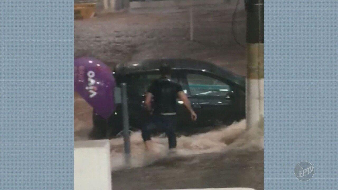 Homem segura carro durante enxurrada em Campinas
