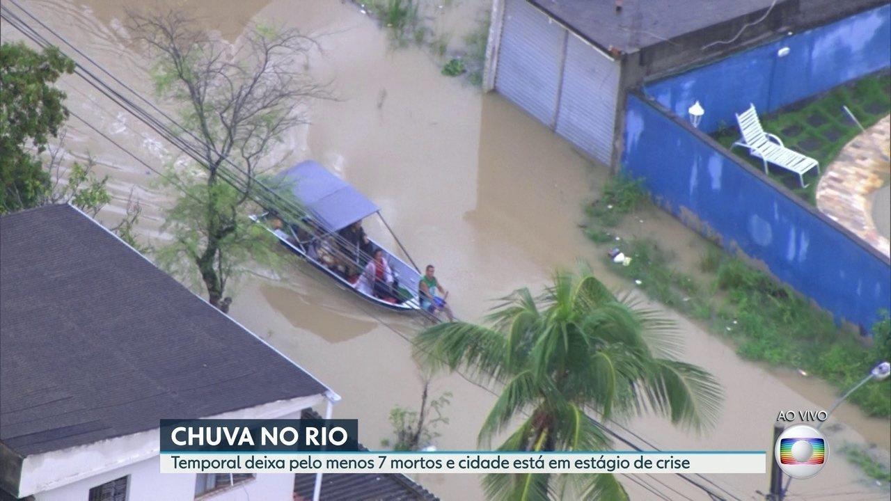 Pessoas se deslocam de barco em área alagada do Jardim Maravilha
