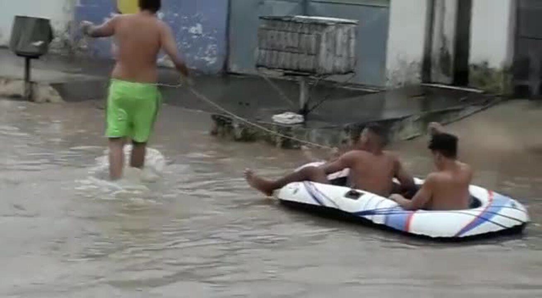 Moradores usam bote após chuva alagar avenida no Grande Recife